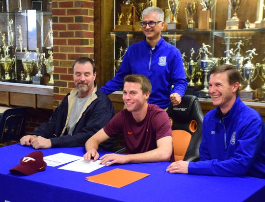 Robert E. Lee's Kyle Stenzel smiles after signing his national letter of intent to play soccer at Virginia Tech on Wednesday, Nov. 14, 2018, at Robert E. Lee High School in Staunton, Va. Behind him is Lee head coach Homes Tehrani, with long-time teacher and coach Mike Guertler to his left and Lee assistant Mike VanHoy to his right.