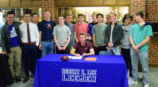 Robert E. Lee's Kyle Stenzel teammates gather behind him after he signed his national letter of intent to play soccer at Virginia Tech on Wednesday, Nov. 14, 2018, at Robert E. Lee High School in Staunton, Va.