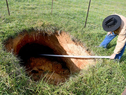 Bobby Whitescarver, an Augusta County farmer and soil conservationist, uses a surveyors rod to measure a sinkhole on Scott Miller's farm in Swoope. He investigates the sinkhole, which is 2.6 miles from the route for the proposed Atlantic Coast Pipeline, at the request of his neighbor on Wednesday, Nov. 14, 2018.