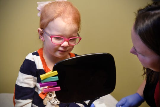 Lizzy Gerads checks out her new ear piercings in a mirror after having the procedure done by Cassidy Bren of Sartell Pediatrics Wednesday, Nov. 14, at the clinic in Sartell.