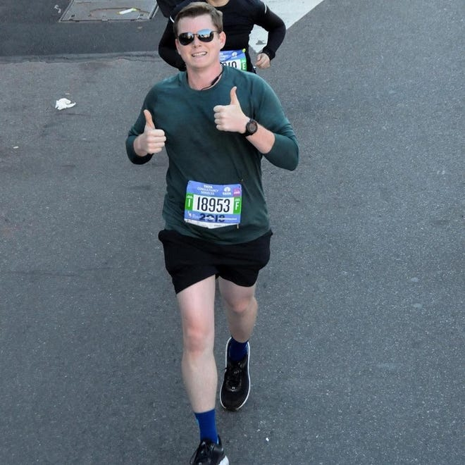 Brian Thedy gives a thumbs up as he runs in the recent New York City Marathon.
