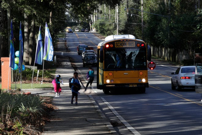 Children get off the bus on North Meridian Road Thursday, Oct. 8, 2018. Leon County Schools will be reducing the number of bus stops along routes beginning next year.