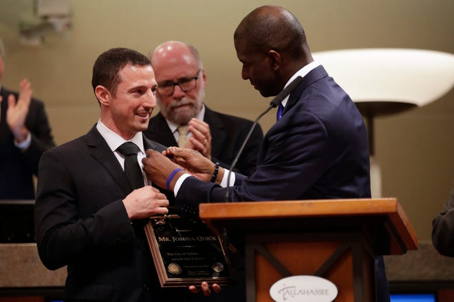 With a standing ovation from those in attendance, Mayor Andrew Gillum presents Joshua Quick with a Key to the City of Tallahassee at a city commission meeting Wednesday, Nov. 14, 2018.