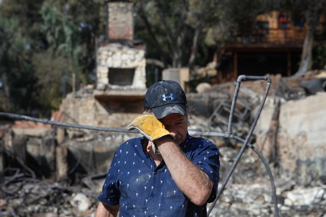 """Roger Kelton wipes his tears while searching through the remains of his mother-in-law's home that burned down by the Woolsey Fire in Agoura Hills. """"We knew it was gone, but I still haven't had my good cry yet,"""" Kelton said. """"I've been trying to be strong for my daughter, my wife and my mother-in-law."""""""