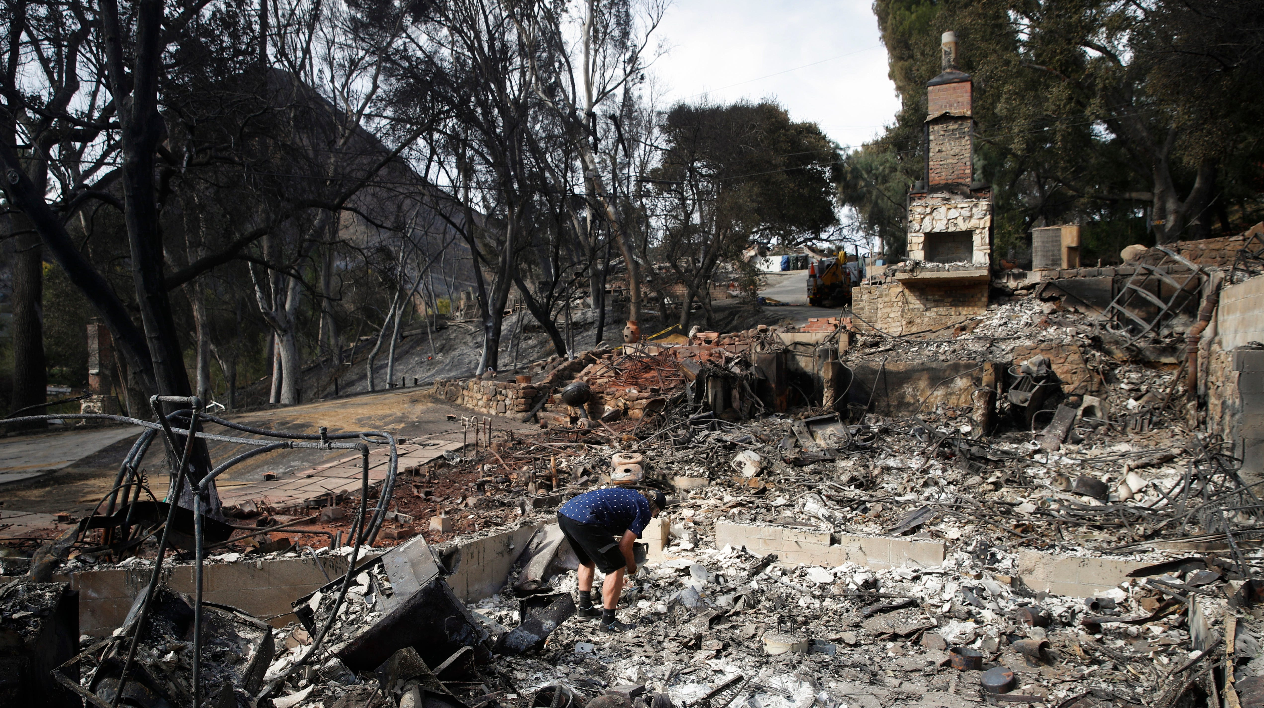 Roger Kelton searches through the remains of his mother-in-law's home leveled by the Woolsey Fire Tuesday in Agoura Hills.
