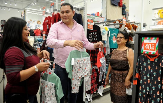 From left, Yenira Luna shops with her cousin Nelson Pacheco and her mom, Josefina Mejia, at Old Navy in the Camarillo Premium Outlets. The outlets are expecting crowds beginning on Thanksgiving Day, when stores open at 6 p.m.