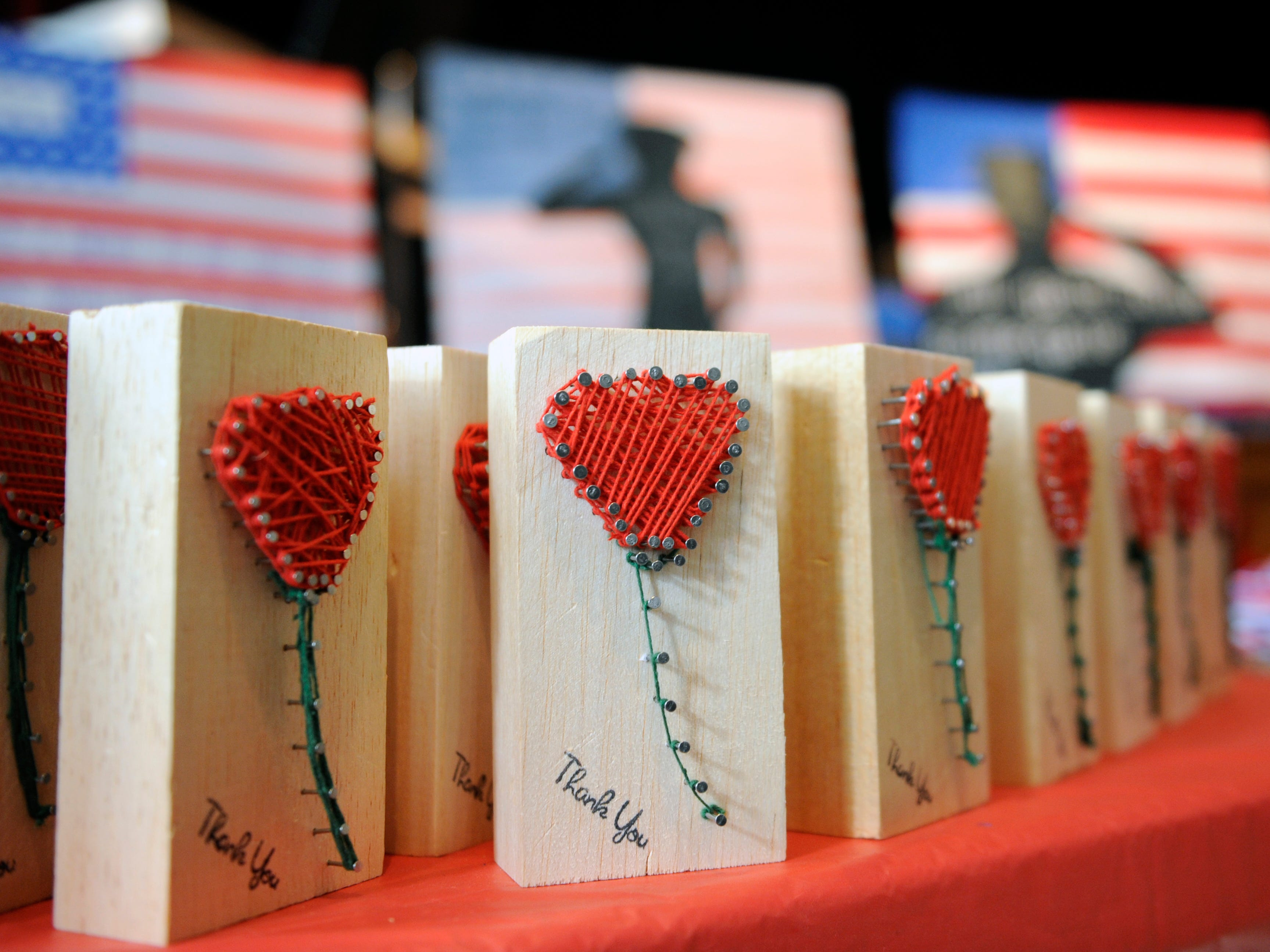 Students handed out pin and thread art representing a rose during a special assembly honoring heroes at Veterans Memorial School on Wednesday, November 14, 2018.