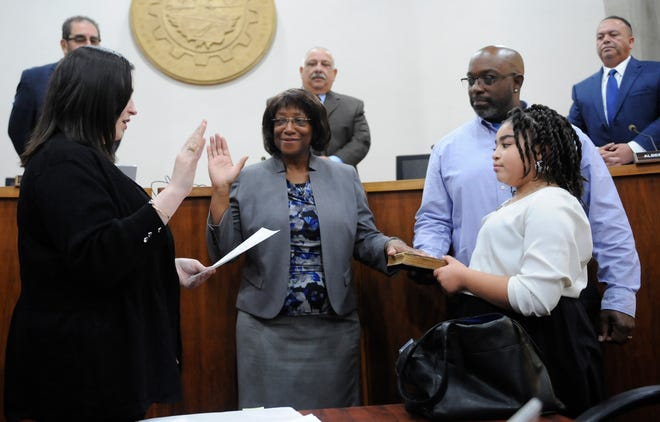 Elizabeth Arthur is sworn in as the newest member of Vineland City Council by Deputy Municipal Clerk Christine Scarpa while her son Dale Arthur Jr., and granddaughter Hannah Garrison, 10, hold the bible at City Hall on Tuesday, November 13, 2018