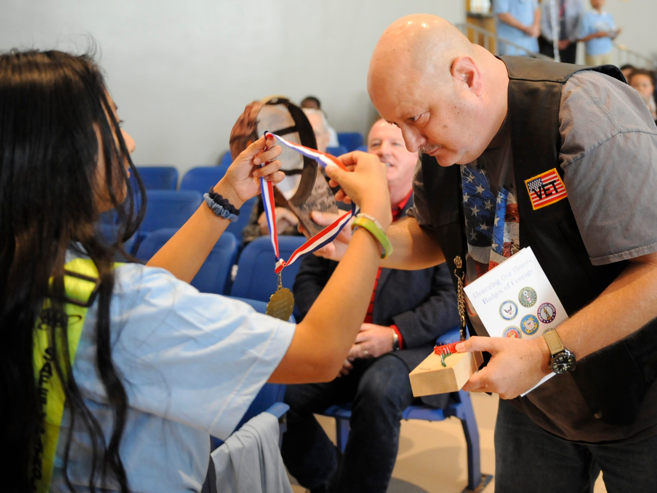 Veterans Memorial School students place medals on veterans who attended a special assembly honoring heroes on Wednesday, November 14, 2018.