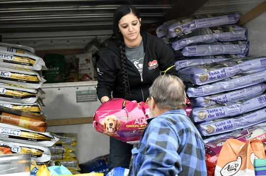 Catheryn Thompson, Butte Human Society adoption coordinator, hands a Camp Fire victim a bag of dog food at the organization's pet supply and food pantry in Chico on Wednesday, November 14, 2018.
