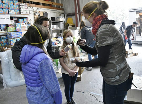 Clarisa Copsey, 8, listens to her mother Leanha Copsey speak to a Butte Human Society employee at the organization's pet supply and food pantry in Chico on Wednesday, November 14, 2018.