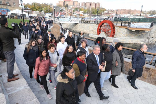 Yonkers Mayor Mike Spano, along with New York State Sen. Andrea Stewart-Cousins, walks with other officials and students from Lincoln High School, as phase 3 of the Saw Mill River Daylighting is opened at Nepperhan Avenue and New Main Street, Nov. 14, 2018.