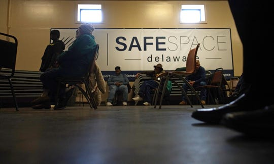Men rest in a common area of SafeSpace Delaware during the afternoon to keep warm from Thursday's falling temperatures.