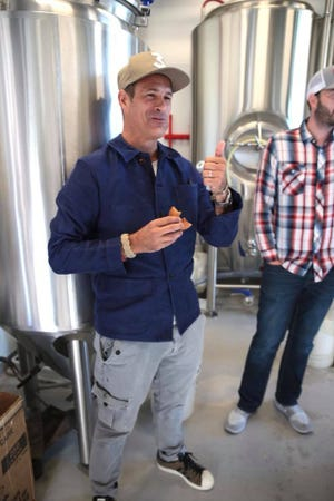 Dogfish Head founder Sam Calagione sneaks an apple cider doughnut from Fifer Orchards while making a new collaborative beer called Have Another Donut. It debuts at the brewery's Rehoboth Beach brewpub on Friday, Nov. 16 at 11 a.m. to help kick off the two-day Analog-A-Go-Go beer and music festival.