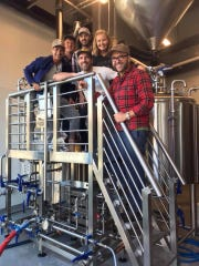 Members of the Dogfish head, Fifer Orchards and Dewey Beer Co. teams pose while brewing their new collaborative doughnut beer, making its debut in Rehoboth Beach and Milton this weekend.