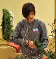 Interfaith Outreach Services Executive Director Kris Gossom decorates for the nonprofit's third annual Oh! Christmas Tree fundraising event to be held Thursday evening at the Forum located on Speedway Ave.