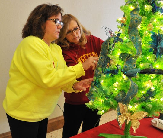 Interfaith Outreach Services volunteers Robin Stuyck, left, and Jana Lane decorate a Christmas tree that will be auctioned to raise money for the nonprofit, which helps families in Wichita and Archer counties that find themselves in temporary financial crisis.
