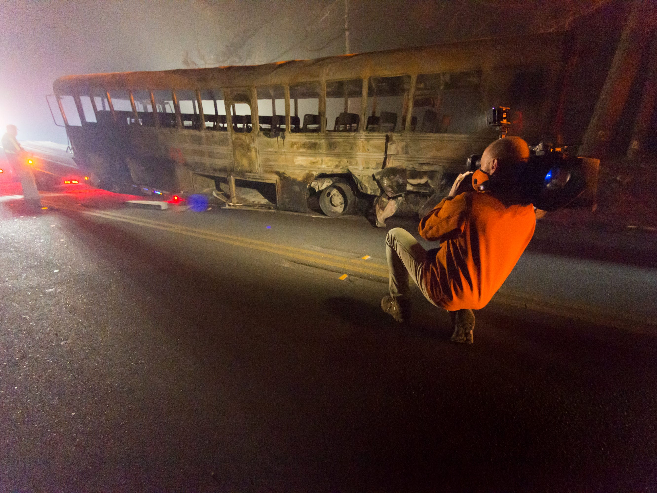 Videographer Scott Eason lights a school bus destroyed by the Camp Fire in Paradise, Calif., Tuesday, Nov. 13, 2018.