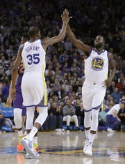 Kevin Durant celebrates with Draymond Green during the first half of a game against the Phoenix Suns.