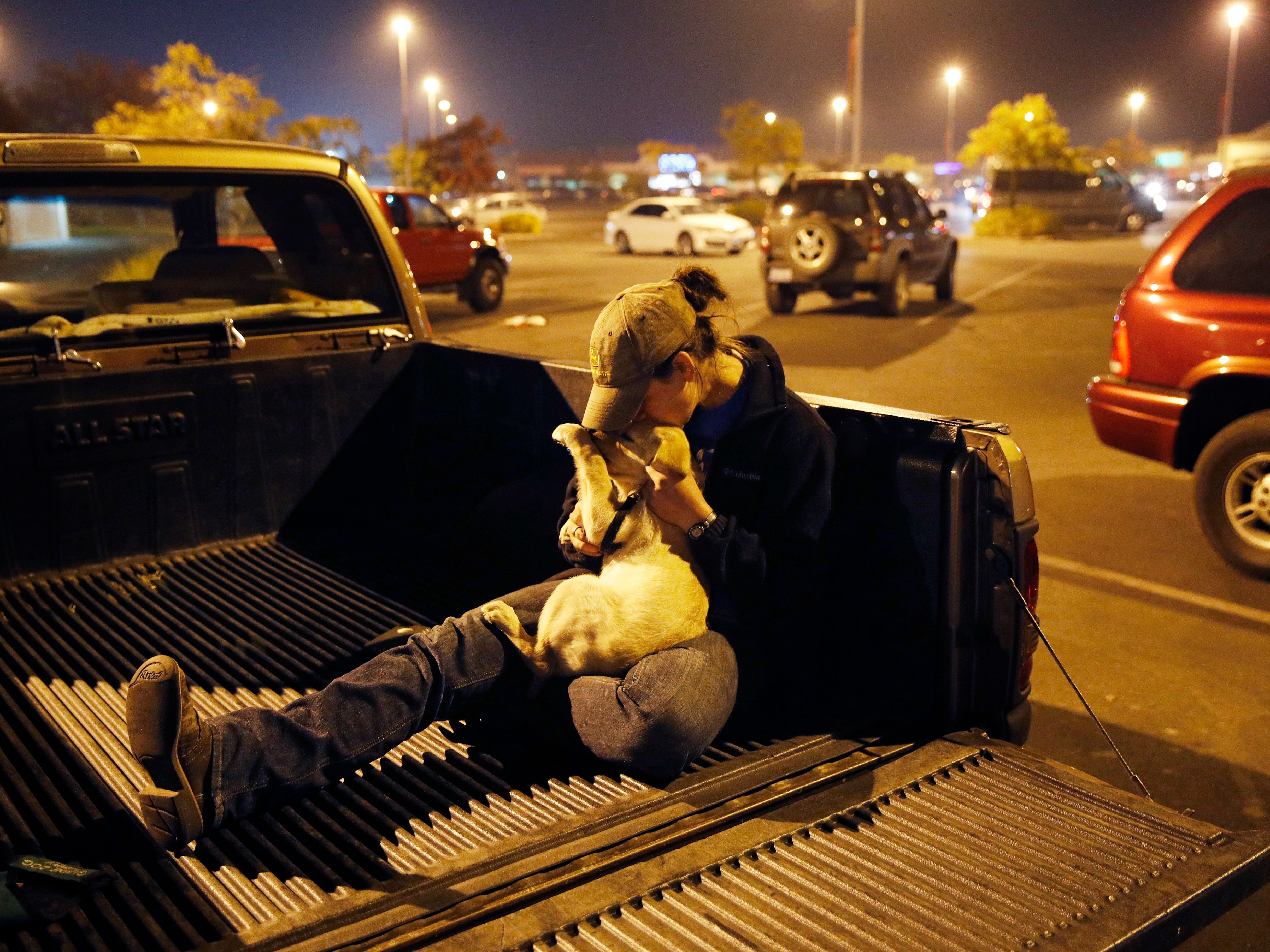 Sarah Gronseth kisses her dog Branch in the bed of a truck in a parking lot, Tuesday, Nov. 13, 2018, in Chico Calif. Gronseth, a teacher, evacuated some of her high school students in her truck as the fire bore down on the high school in Paradise, Calif. She lost her home in the fire.