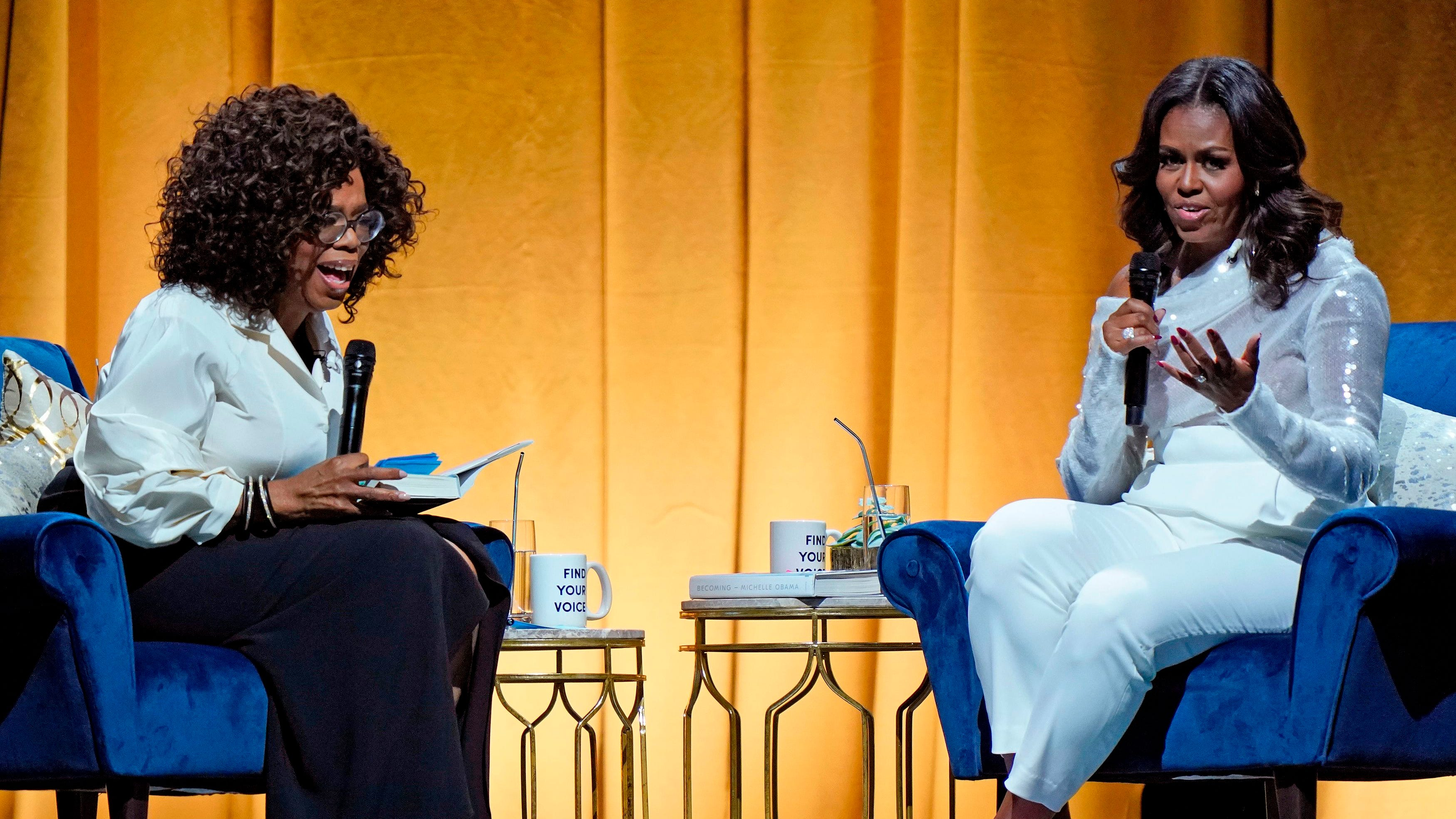 "Former US first lady Michelle Obama (R) and Oprah Winfrey speak during the opening of her multi-city book tour at the United Center in Chicago, November 13, 2018. - Former US first lady Michelle Obama's book, ""Becoming,"" hits stores on Tuesday. Obama, 54, will head out on a multi-city arena tour to promote the memoir, with celebrity friends like Oprah Winfrey and Reese Witherspoon tapped to moderate the events. (Photo by JIM YOUNG / AFP)JIM YOUNG/AFP/Getty Images ORG XMIT: Former U. ORIG FILE ID: AFP_1AT7X0"