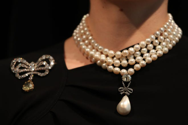 A model wears The 'Queen Marie Antoinette's Pearl' with an estimated value of $1,000,000-2,000,000 on Queen Marie Antoinette's pearl and diamond necklace, together with a Queen Marie Antoinette's diamond brooch.