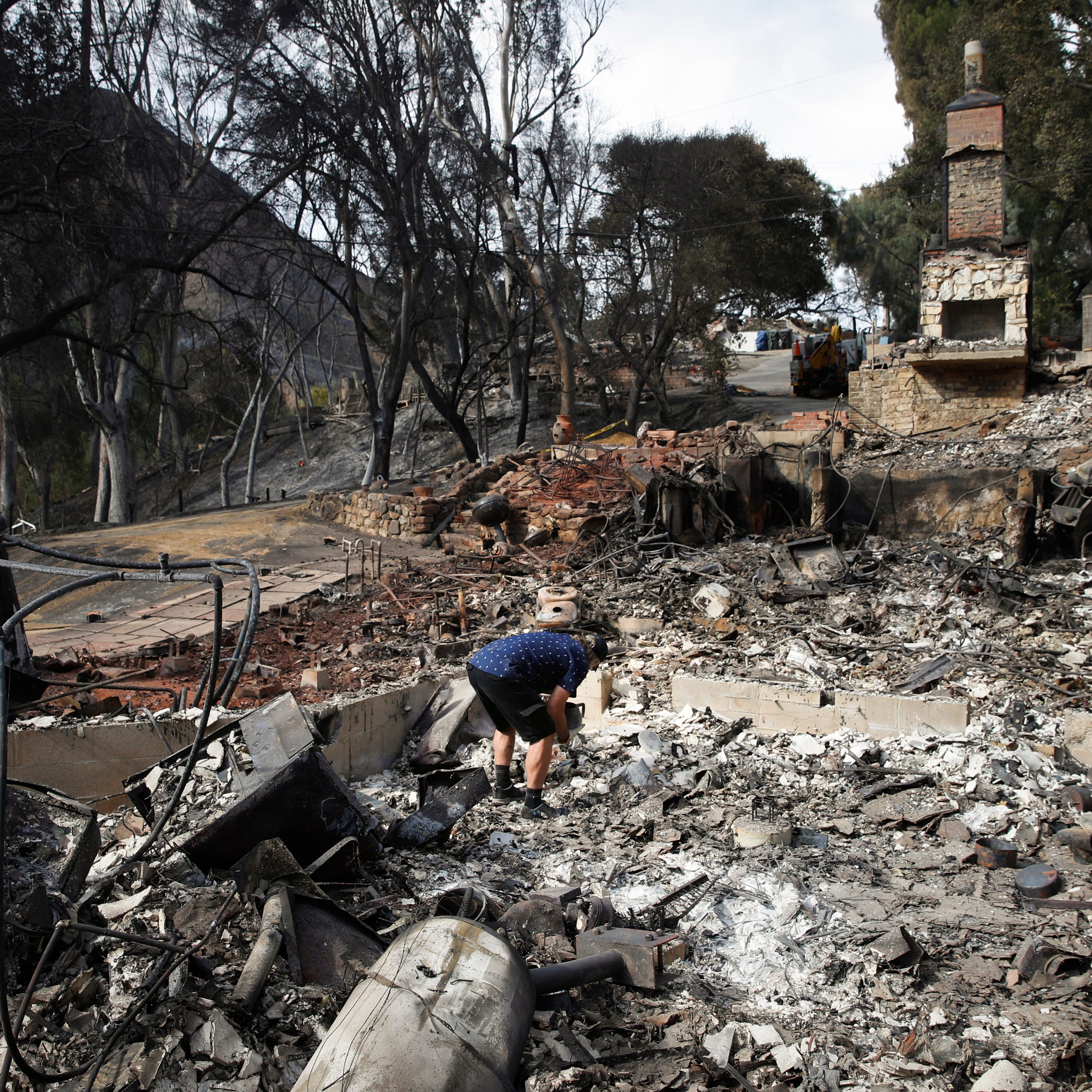 Roger Kelton searches through the remains of his mother-in-law's home leveled by the Woolsey Fire, Tuesday, Nov. 13, 2018, in the southern California city of Agoura Hills.