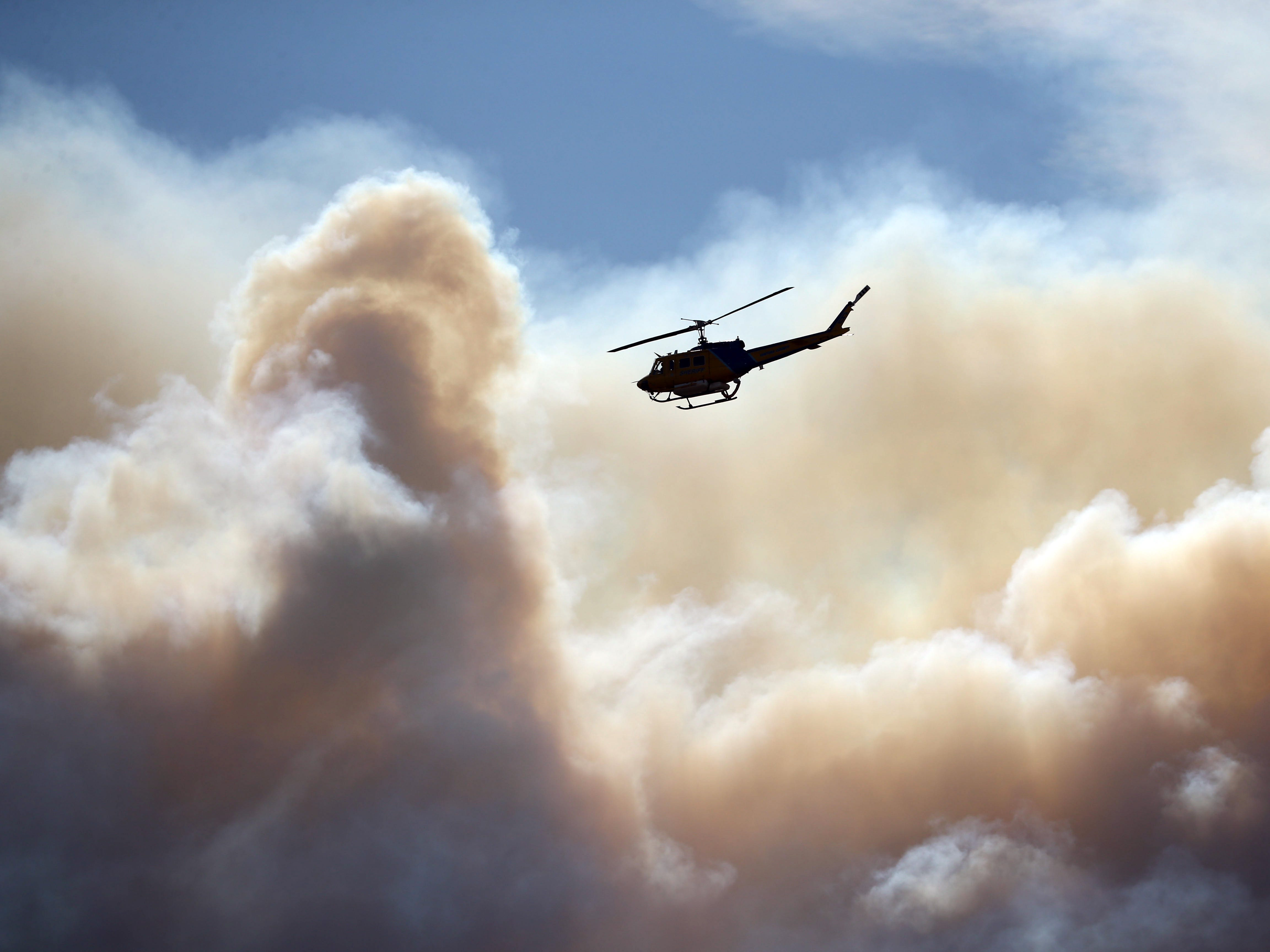 A helicopter flies near the Woolsey Fire burning in the Santa Monica Mountains National Recreation Area in Newbury Park, Calif. on Nov. 13, 2018.