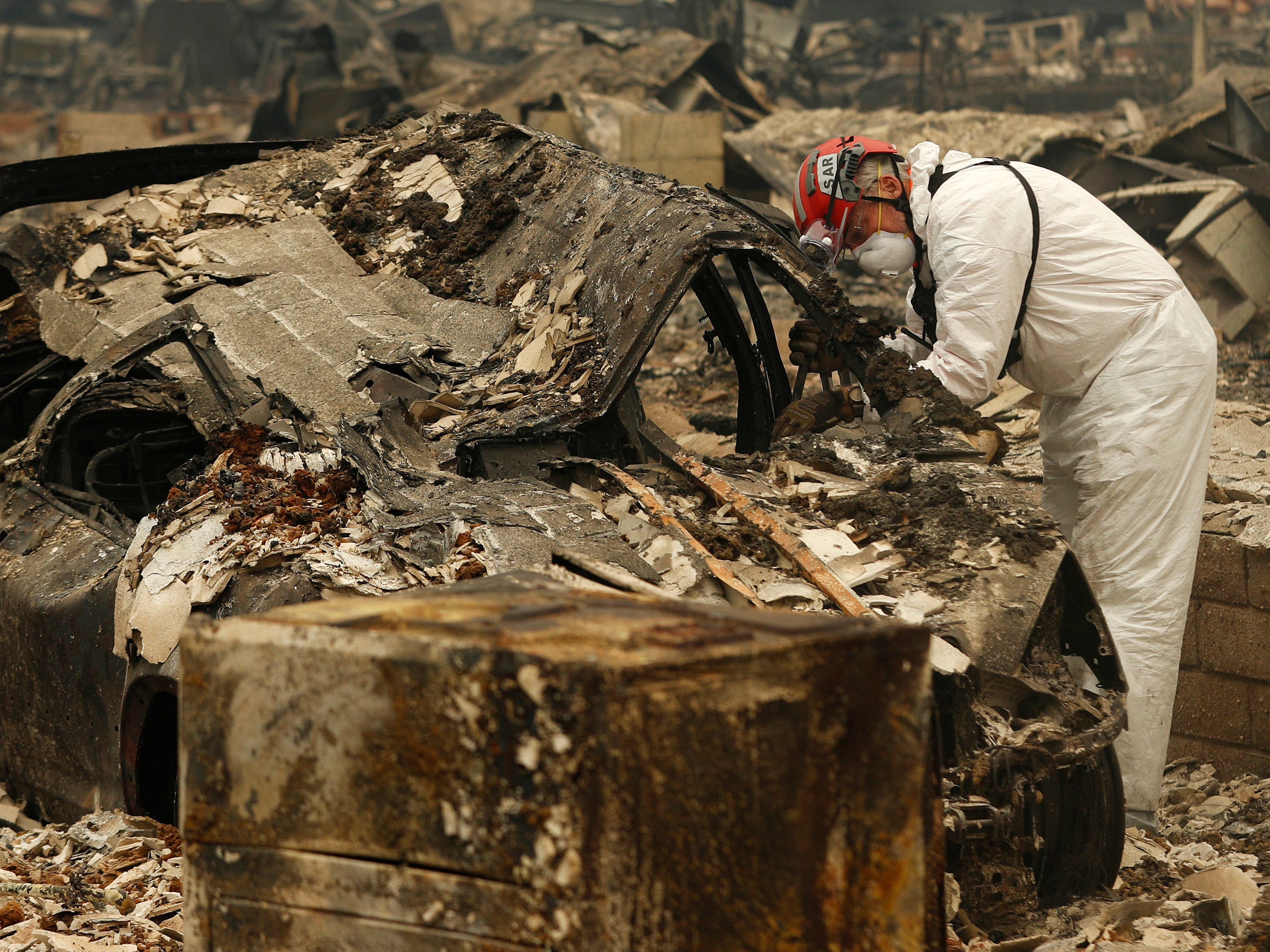 A search and rescue worker searches a car for human remains at a trailer park burned out from the Camp Fire, Tuesday, Nov. 13, 2018, in Paradise, Calif.