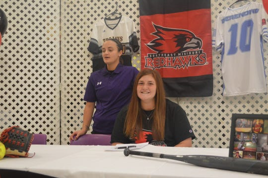 ASH softball catcher Jaislyn Merendino (right) smiles as Lady Trojans coach Logan Hebert speaks about her Wednesday. Merendino signed her NLI with Southeast Missouri.