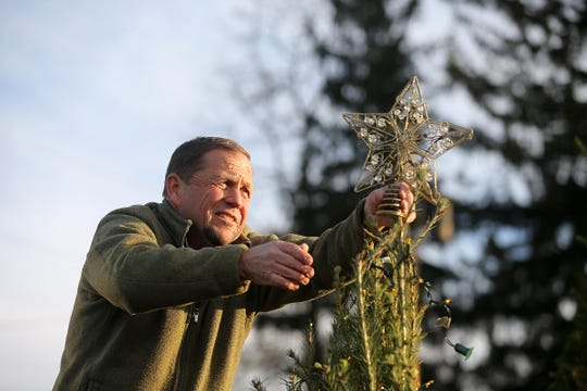Gary DeFelice, owner of Cedar Hill Farm and Nursery, places a start on top of a tree as Natalie Gorsegner, 9, a childhood cancer survivor, and her sister Hannah Gorsegner, 11, decorate the two Christmas trees they have been caring for since they sprouted at Cedar Hill Farm and Nursery in Middletown, NJ Wednesday, November 14, 2018.