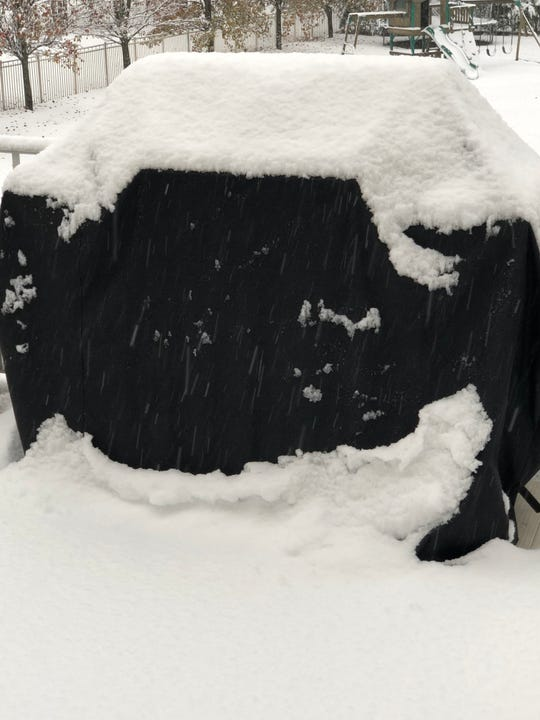Snow covered the deck and barbecue grill at a home in Jackson.