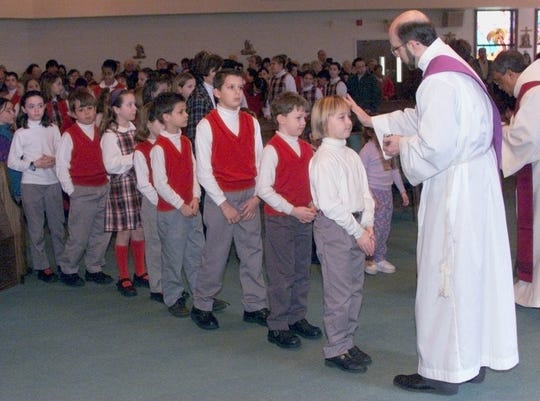 Deacon John Klincewicz administers ashes to the foreheads of students who attend school at Holy Innocents Roman Catholic Church in Neptune during the Ash Wednesday services in 2001.