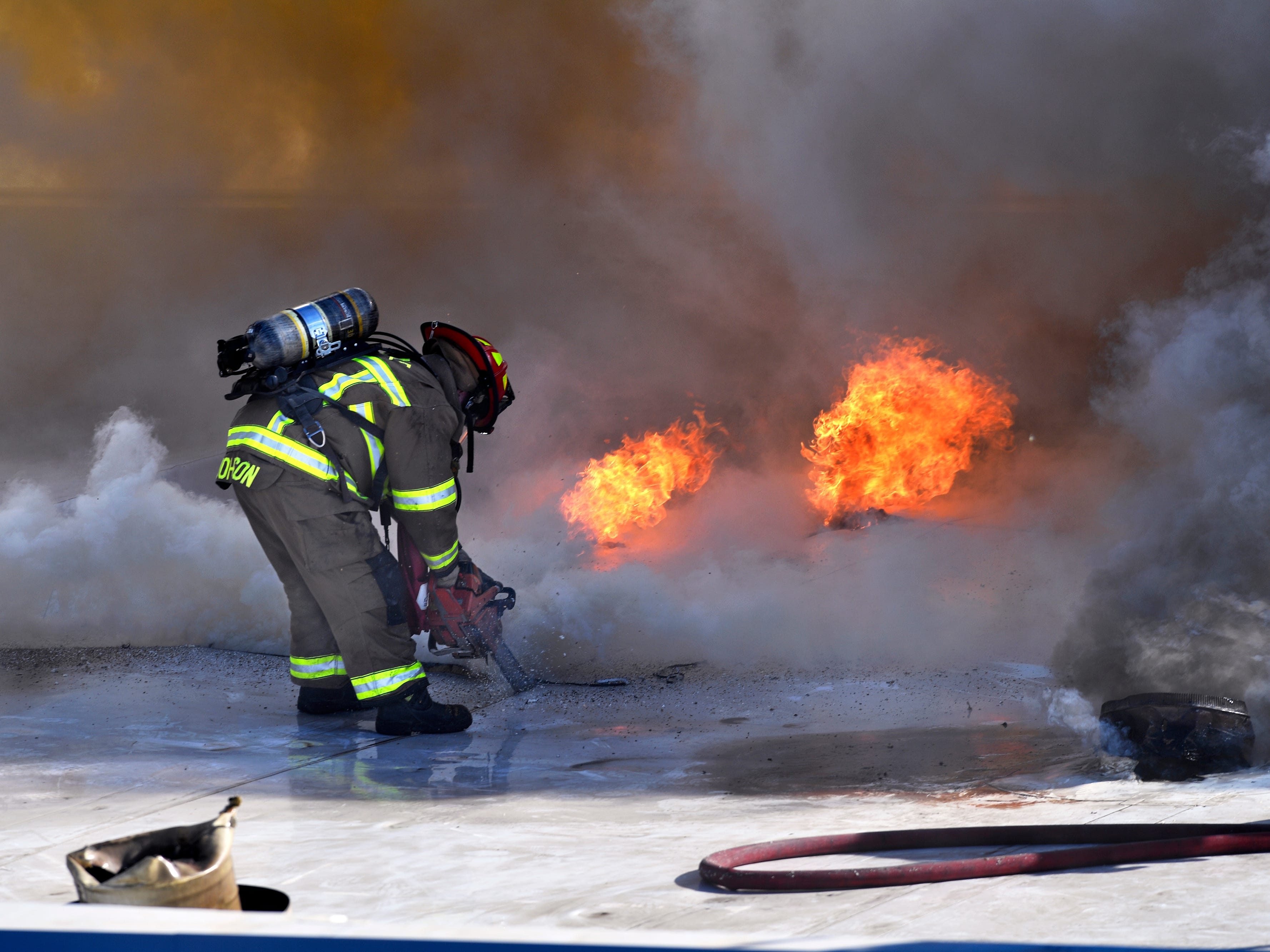 An Abilene firefighter cuts a hole in the roof of the Abilene Reporter-News as the department responds to a two-alarm blaze at the Thursday Nov. 15, 2018. The fire was called in at 9:20 a.m., at one time all three of the city's ladder trucks were employed during the fight.,