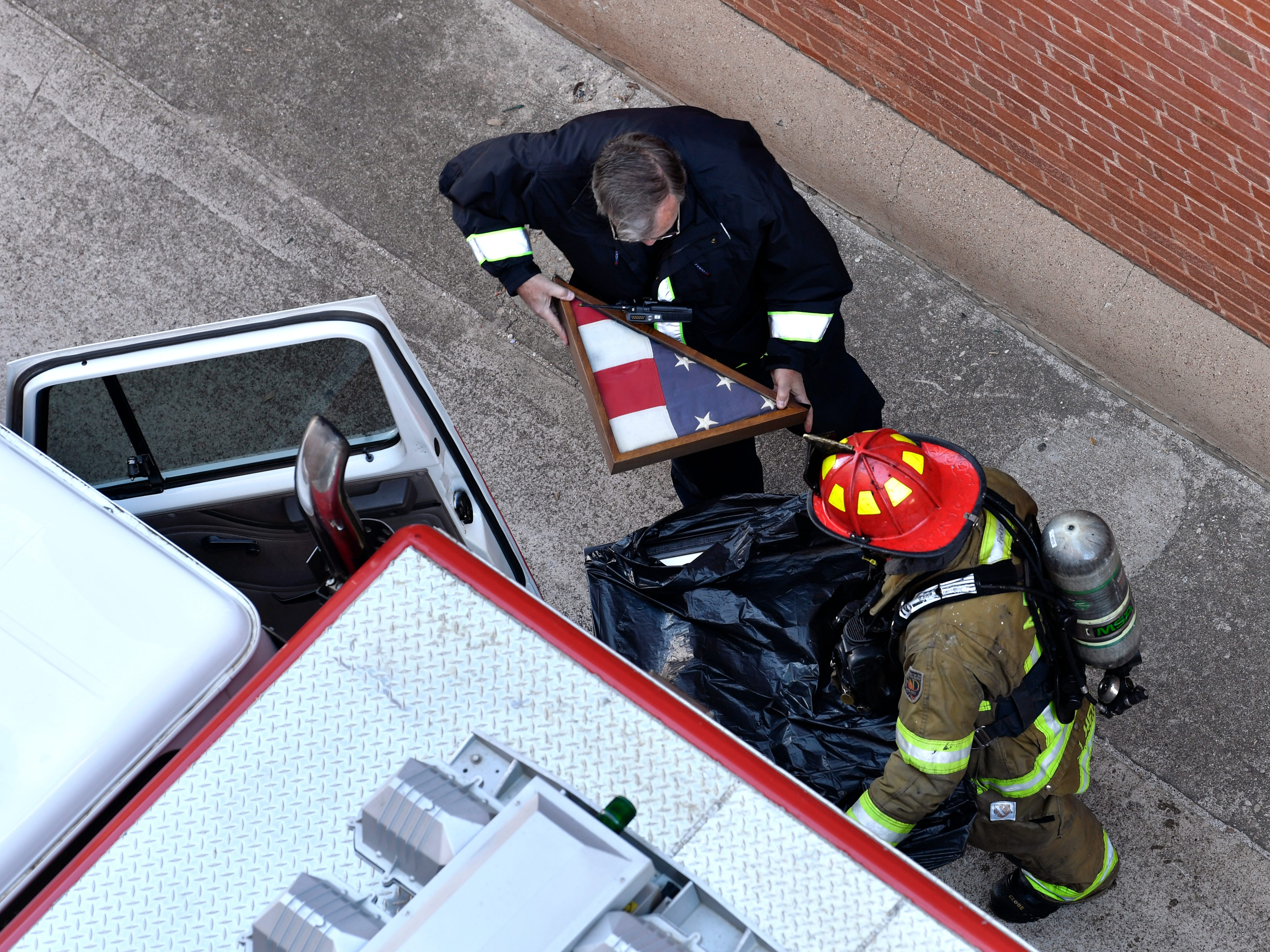 Fire department personnel place a shadowbox and picture recovered by the firefighters inside a fire engine parked near the Grace Museum. Abilene firefighters respond to a two-alarm blaze at the Abilene Reporter-News Thursday Nov. 15, 2018. The fire was called in at 9:20 a.m., at one time all three of the city's ladder trucks were employed during the fight.,