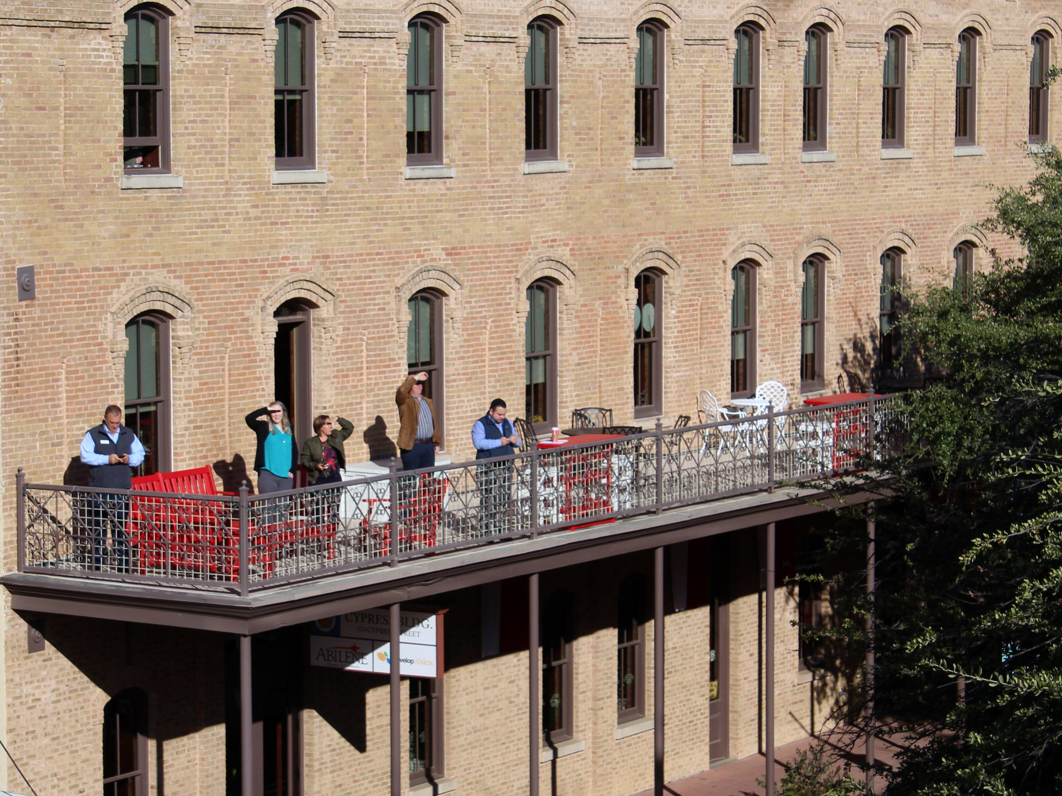 People watch from the Abilene Chamber of Commerce balcony as firefighters investigate a sparking electrical system on the roof of the Abilene Reporter-News Thursday Nov. 15, 2018. The two-alarm fire was called in at 9:20 a.m.