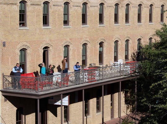 People watch from the Abilene Chamber of Commerce balcony as firefighters investigate a fire at the Abilene Reporter-News on Nov. 15, 2018. The DCOA, which also offices in the building, is purchasing the downtown icon.