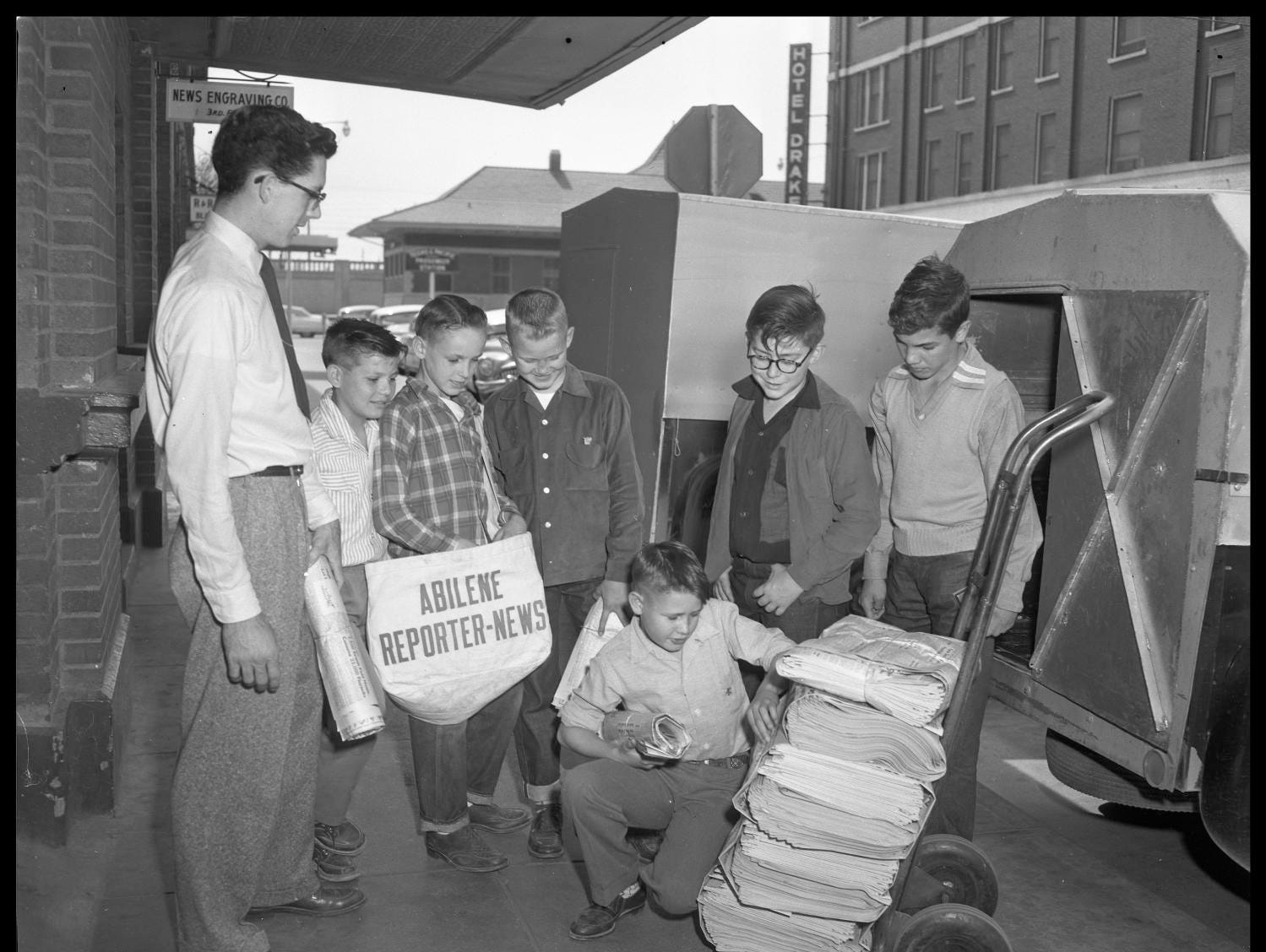 """A photo of the """"Abilene Reporter-News Boys"""" and a man standing on the sidewalk. From 1955."""