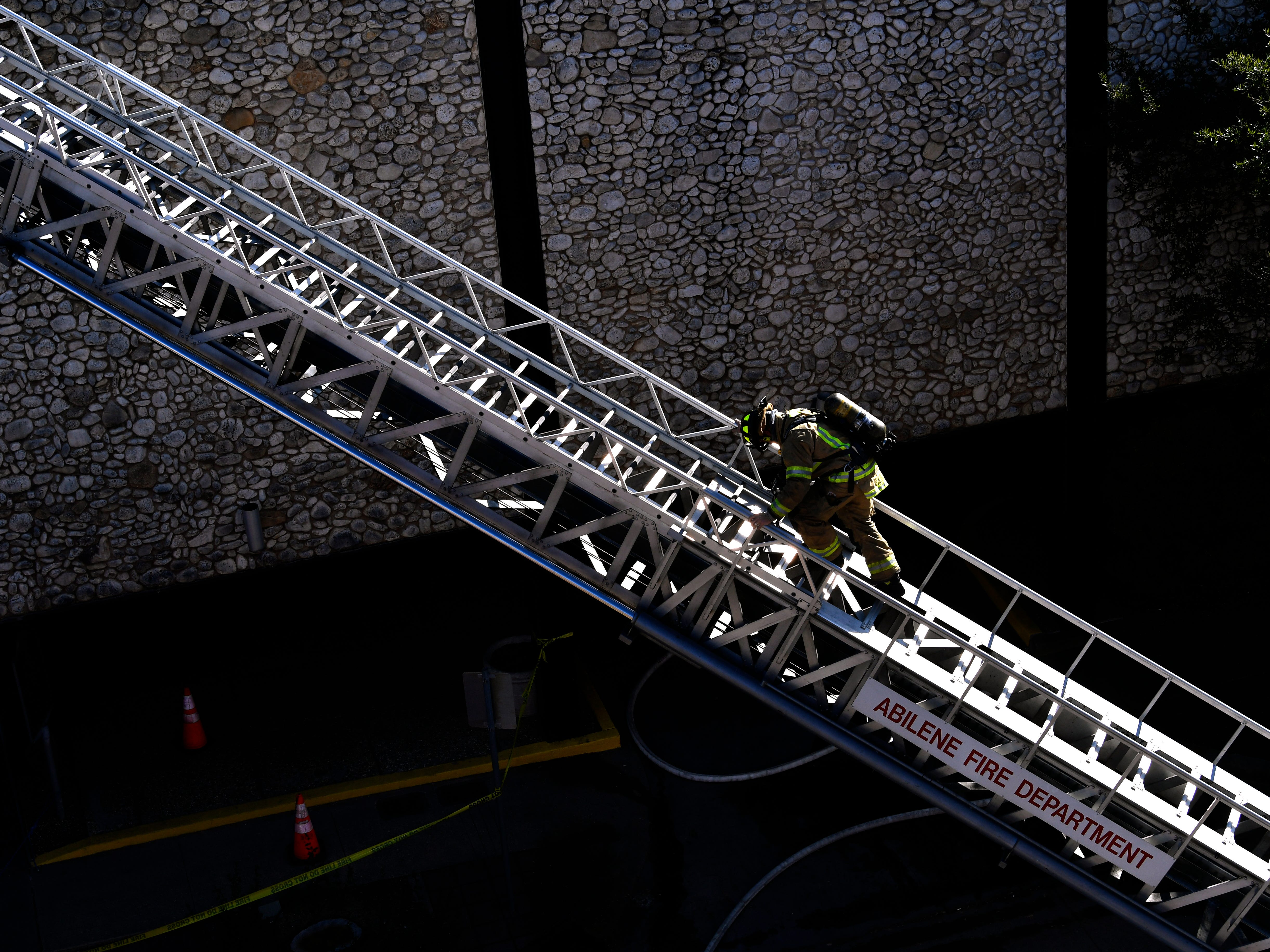 An Abilene firefighter climbs down a ladder while responding to a two-alarm blaze at the Abilene Reporter-News Thursday Nov. 15, 2018. The fire was called in at 9:20 a.m., at one time all three of the city's ladder trucks were employed during the fight.