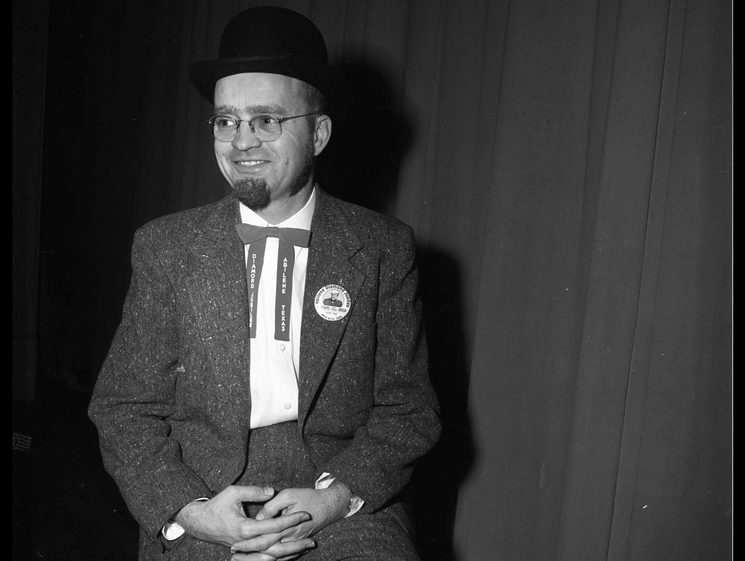 """An April 1956 portrait of Ed Wishcamper, former Abilene Reporter-News editor. He is wearing a suit and hat and a tie that says, """"Diamond Jubilee, Abilene Texas."""" A button on his suit says, """"Abilene Diamond Jubilee, Brothers of the Brush,"""