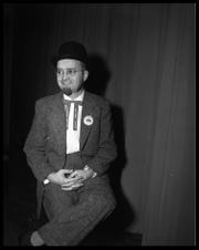 "An April 1956 portrait of Ed Wishcamper, former Abilene Reporter-News editor. He is wearing a suit and hat and a tie that says, ""Diamond Jubilee, Abilene Texas."" A button on his suit says, ""Abilene Diamond Jubilee, Brothers of the Brush,"