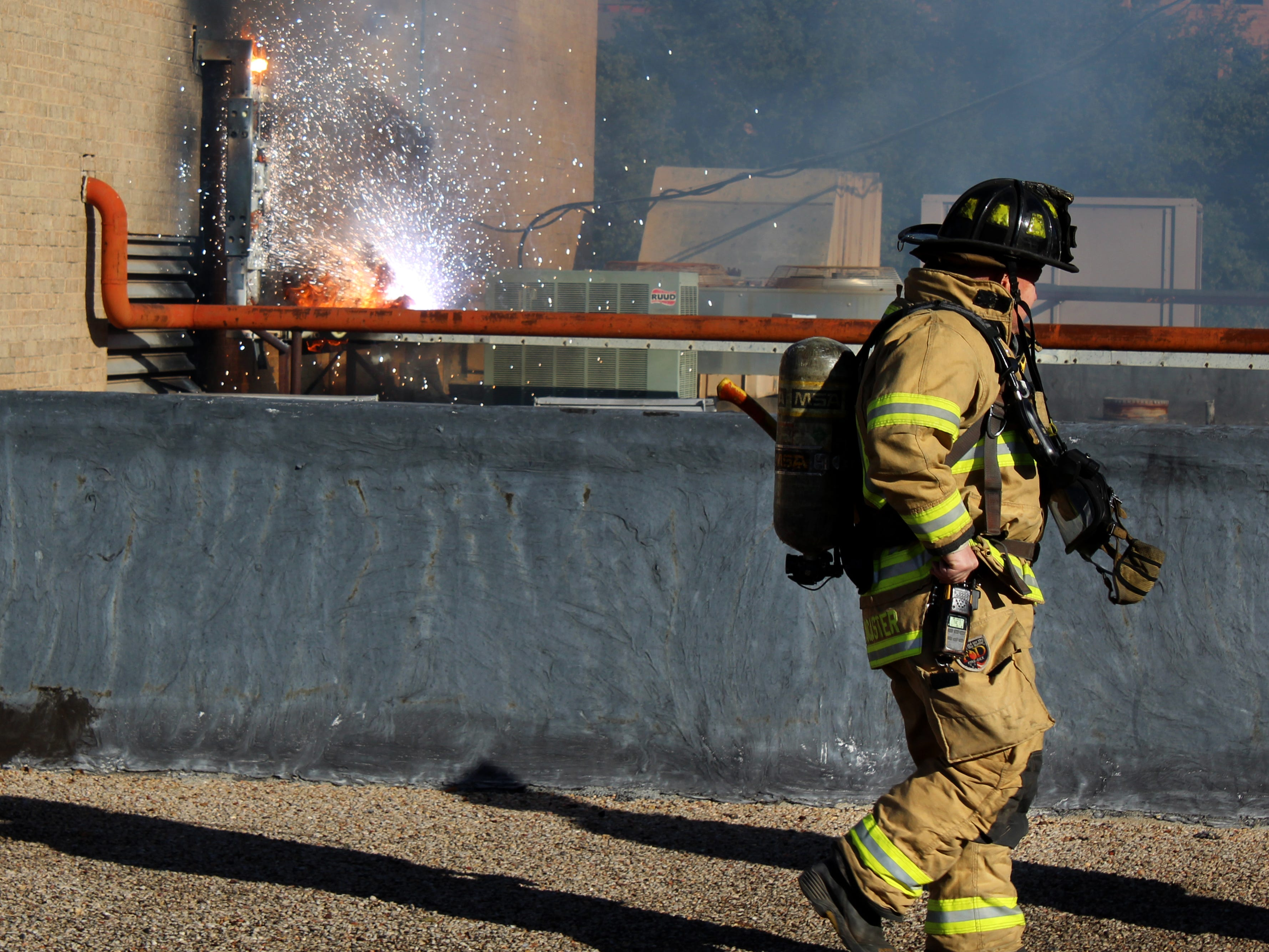 Sparks fly from the east side of the Abilene Reporter-News utility room as a firefighter searches the roof for any more trouble spots Thursday Nov. 15, 2018. The sparks developed into a two-alarm fire, forcing the evacuation of the newspaper.