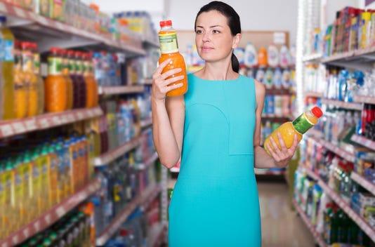Woman Choosing Fruit Juice On Supermarket