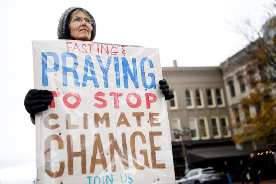 Kendall Hale holds a sign as she supports her husband, Steve Norris, in his fast and helps raise awareness about climate change at Vance Monument Thursday. The group, which has been demonstrating at the site even in the rain, invites the public to join them in a ceremony daily at noon through Nov. 21.