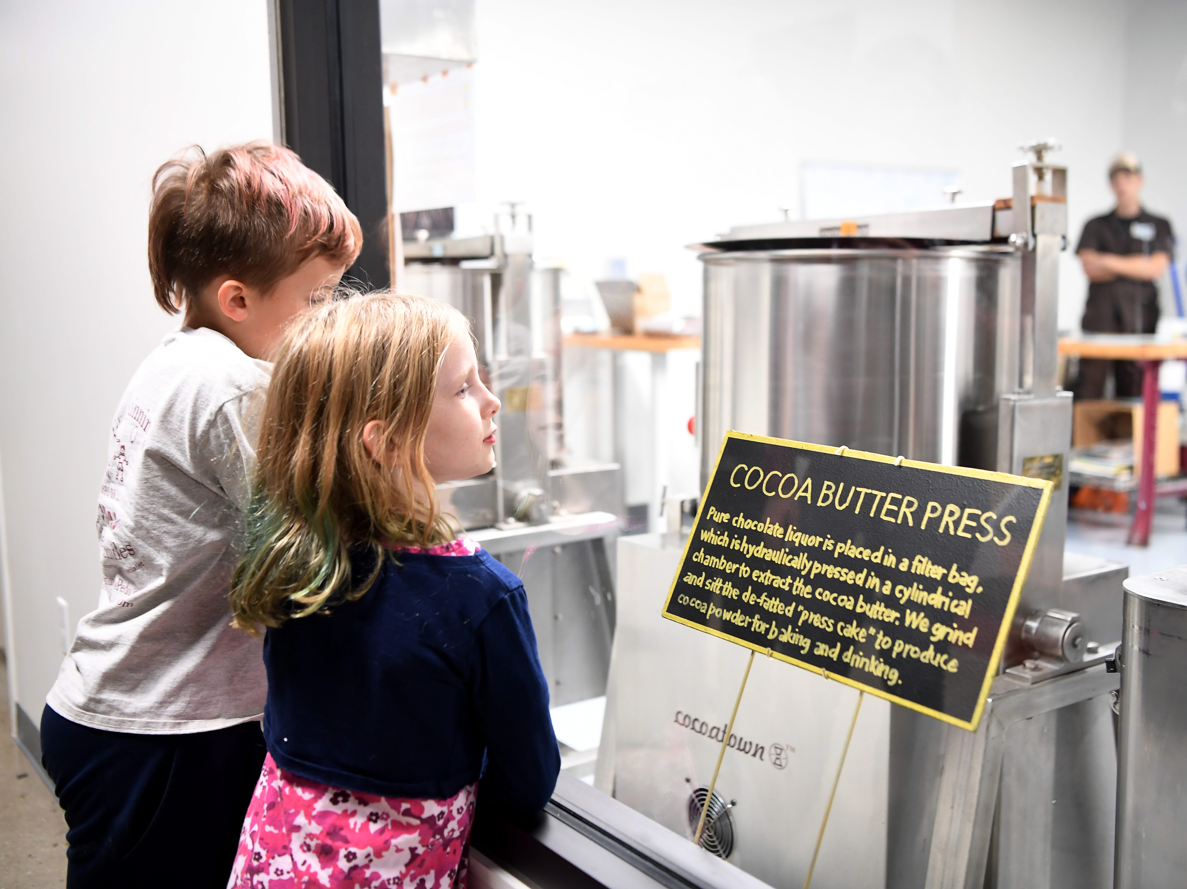 Siblings Riley Bartholic, 9, left, and Tess, 7, watch the cocoa butter press at the French Broad Chocolate Factory's new location Nov. 14, 2018.