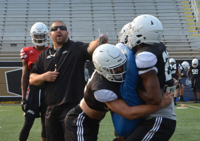 Western Michigan defensive coordinator Tim Daoust runs a drill during the first fall practice on August 14, 2018.