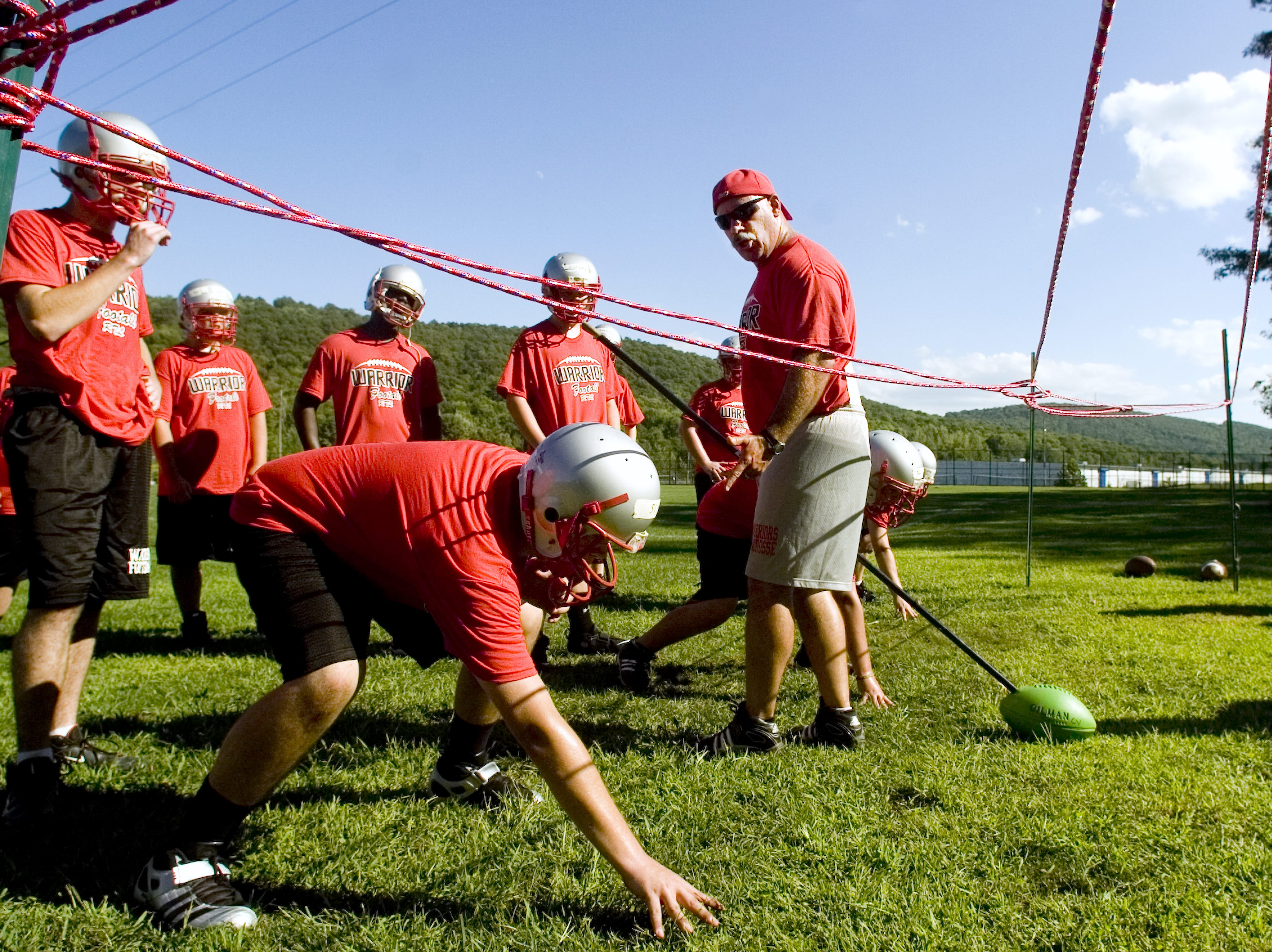 From 2010: The Chenango Valley High School Varsity football team takes instruction from Mike Turna, the team's line coach, during the first day of practice on Monday, late afternoon.