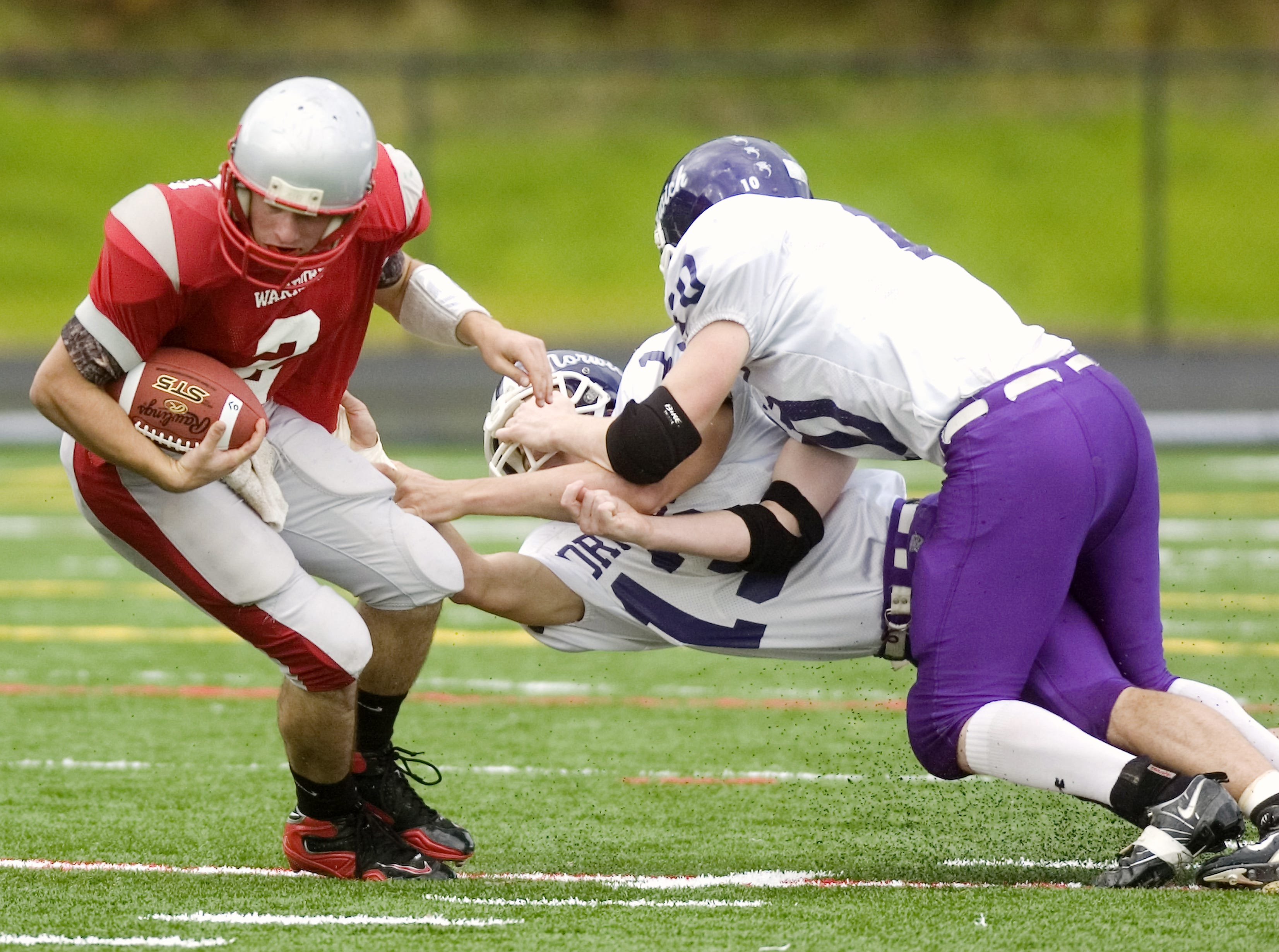 From 2009: Norwich's Morgan Cleveland, right, and Mike Reilly team up to take down Chenango Valley's Ricky Ruffo in the first quarter of Saturday's game at Greene.