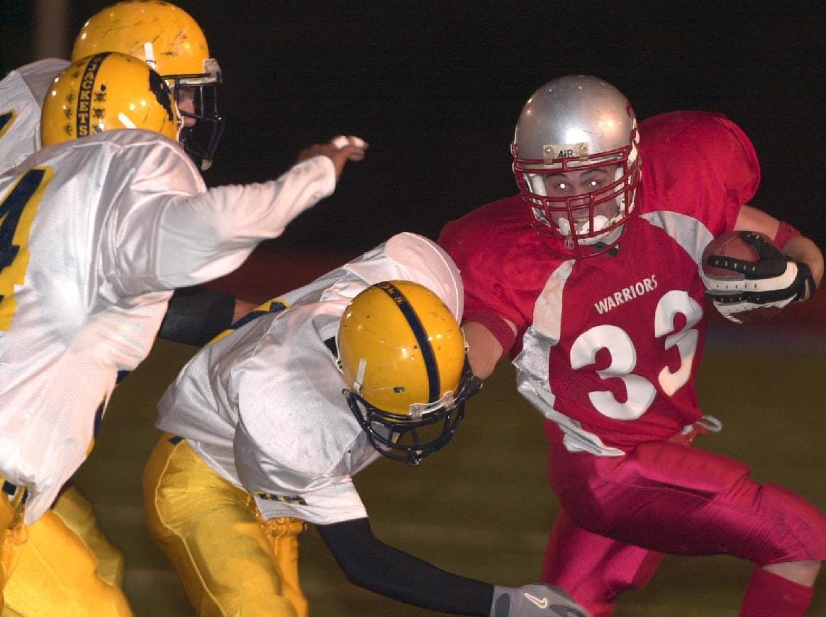 From 2001: Chenango Valley's Josh Burke gives a straight arm to Oneonta's Joffre Alvarez as he looks at the other defenders in the second quarter at Alumni field in Binghamton Friday night.