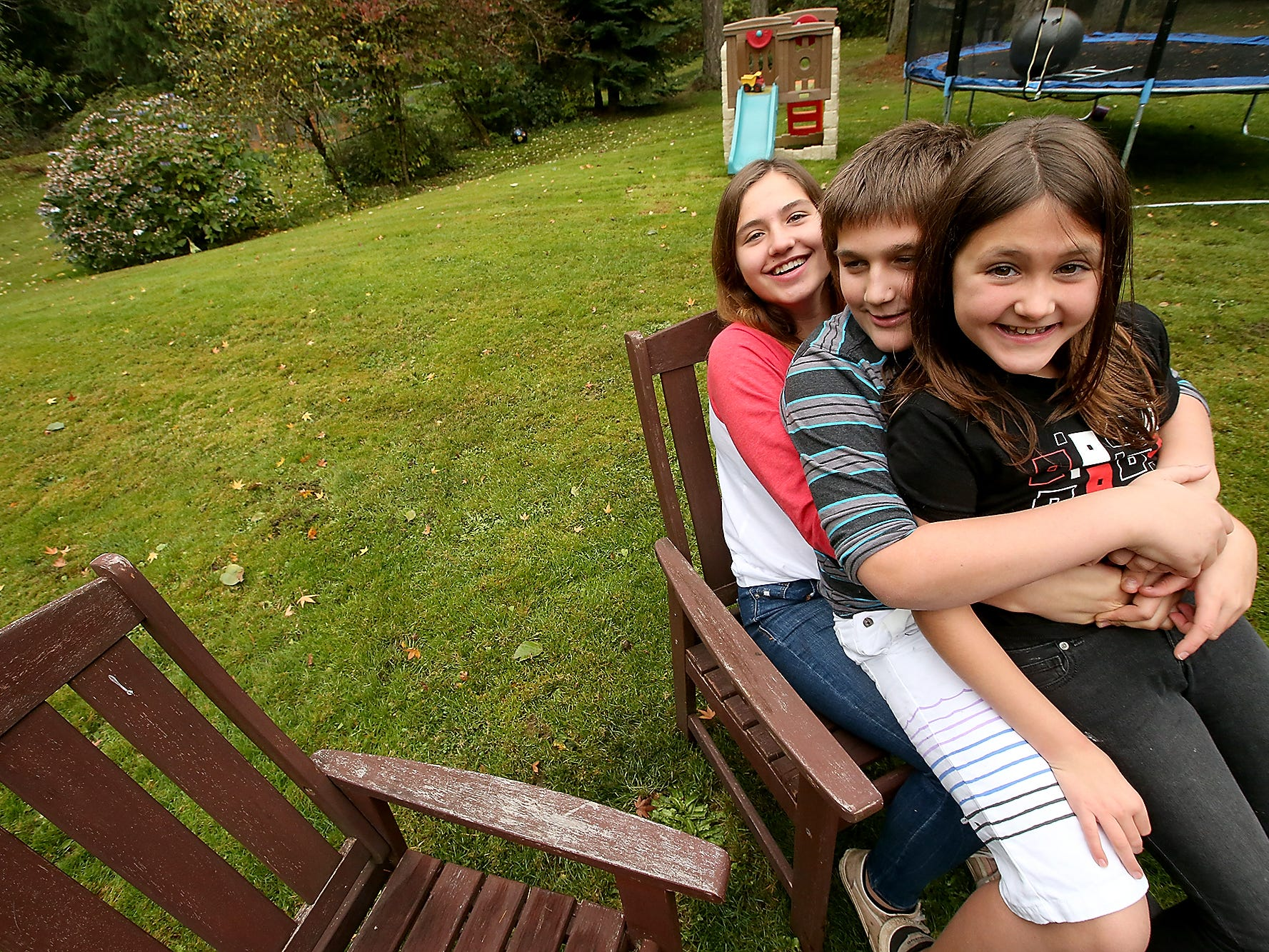 The Alcover siblings (back to front) Kylie, 15, Gavin, 11, and Phoenix, 9, jokingly sit in one lawn chair for a portrait on Wednesday, November 14, 2018. The close-knit siblings from California lost their home in the Paradise fire and are staying with family friends Amber and Douglas Shaw isn Suquamish while their parents work things out in California.